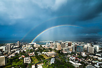 An aerial view of a double rainbow over O'ahu's downtown Honolulu, with the Hawai'i State Capitol in the center of the frame.