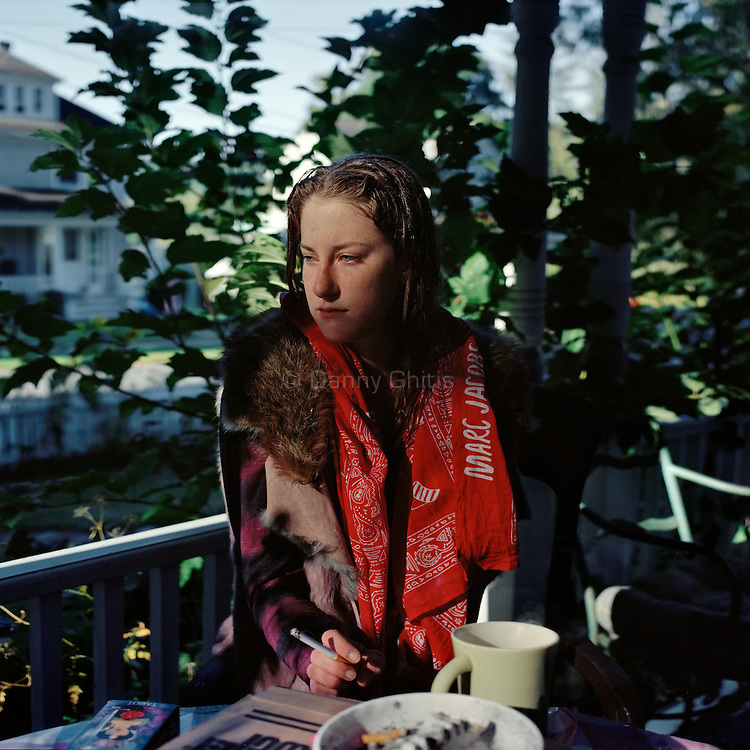 A young woman sits on the porch of her halfway house for recovering addicts before a workday at the local flower shop in Millerton, NY.