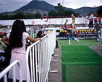 A girl watching lucha libre.  It is very common for a family to bring the kids to these events. ecatepec, Estado de Mexico.  June 2004