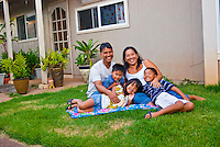 Local part Hawaiian family with mom, dad and three young children sitting in yard in front of their home