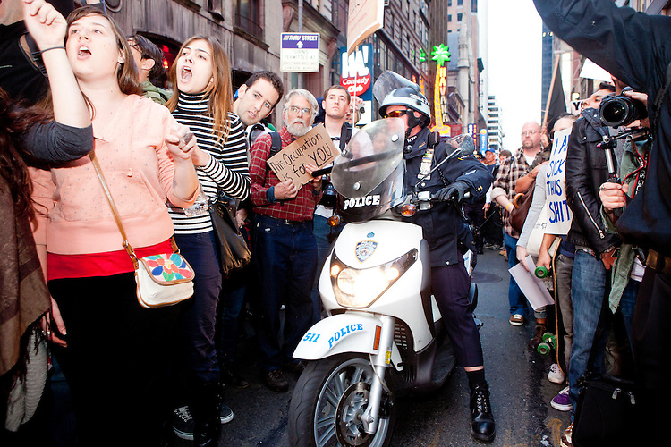 """Policemen on scooters are forced to retreat after failing to control a crowd of protesters with """"Occupy Wall Street"""" at Times Square on October 15, 2011 in New York City.  While crowd estimates numbered in the tens of thousands, police tactics (including nets, motor scooters, barricades, arrests, and intimidation by riders on horseback) prevented the crowd, which had been split up, from joining together as one in the middle of Times Square."""