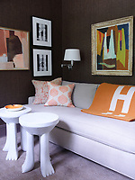The study walls have a textured covering in a browny grey and the paintings and soft furnishing provide accents of warm orange tones; a comfortable sofa provides the seating and two funky side tables stand nearby.