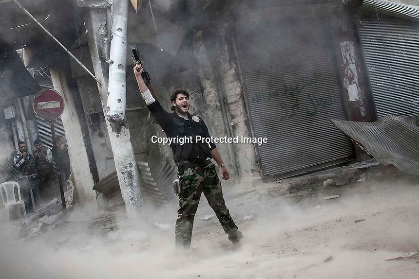 In this Sunday, Nov. 04, 2012 photo, a rebel fighter belonging to the Qatebee Sokor Al-Islam claims for victory after he fires an RPG over a building where Syrian troops loyal to President Bashar Al-Assad hide while they attempt to gain terrain forward the rebel lines during heavy clashes in the nearby Qastal Al-Harami battlefield in the Jdeide district of Aleppo, the Syrian's largest city. (AP Photo/Narciso Contreras).