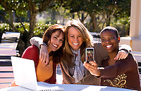 Mixed ethnic women friends relaxing at home laughing with cell phone camera I Phone in sunshine with computer