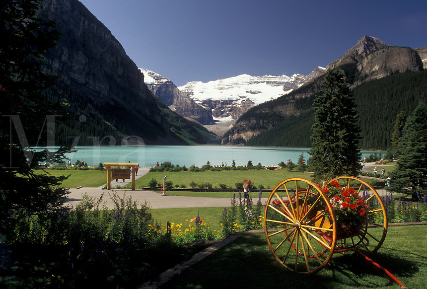 AJ3640, Banff National Park, Lake Louise, Alberta, Canada, Canadian Rockies, Rocky Mountains, Picturesque view of beautiful Lake Louise with the snow-capped mountains in the distance in Banff National Park in the province of Alberta. Two wheeled cart with flowers in the foreground.