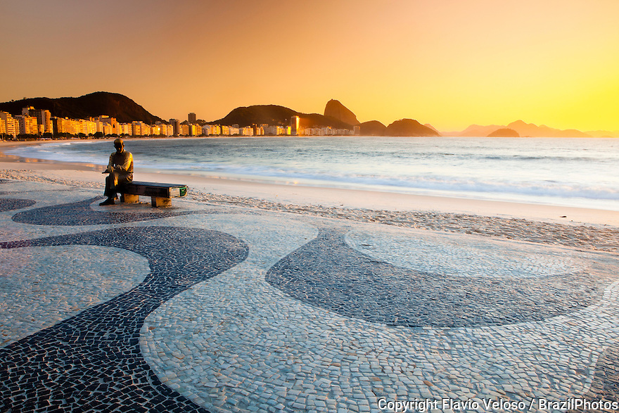 Brazilian poet Carlos Drummond de Andrade statue at Copacabana beach sidewalk, Rio de Janeiro, Brazil. The Copacabana promenade is a pavement landscape in large scale ( 4 kilometres long ) having a black and white Portuguese pavement design by Roberto Burle Marx, a geometric wave.
