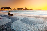 Brazilian poet Carlos Drummond de Andrade statue at Copacabana beach sidewalk, Rio de Janeiro, Brazil. The Copacabana promenade is a pavement landscape in large scale ( 4 kilometres long ) having a black and white Portuguese pavement design by Roberto Burle Marx, a geometric wave.