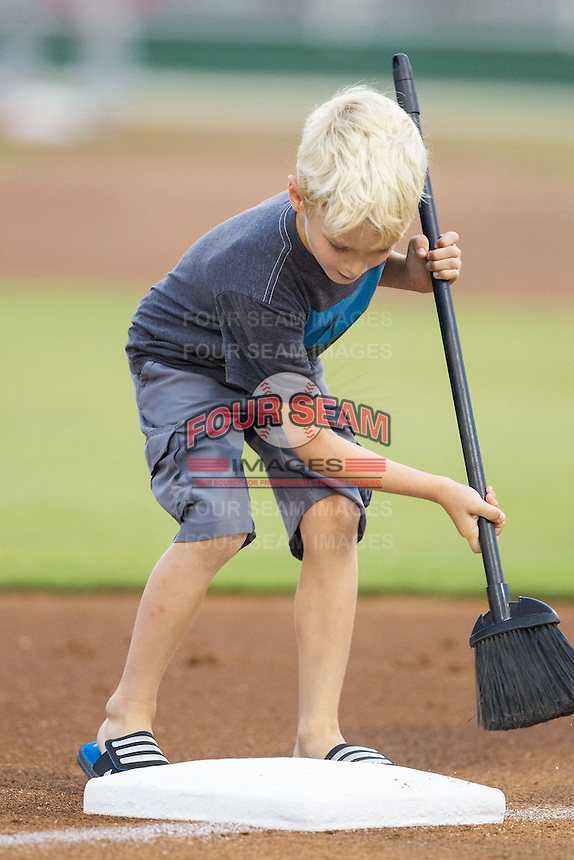 A young fan cleans third base between innings of the South Atlantic League game between the Delmarva Shorebirds and the Kannapolis Intimidators at CMC-NorthEast Stadium on July 3, 2014 in Kannapolis, North Carolina.  The Shorebirds defeated the Intimidators 6-5. (Brian Westerholt/Four Seam Images)