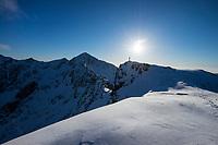 Silhouette of hiker on summit of Kleivheia in winter, Vestvågøy, Lofoten Islands, Norway
