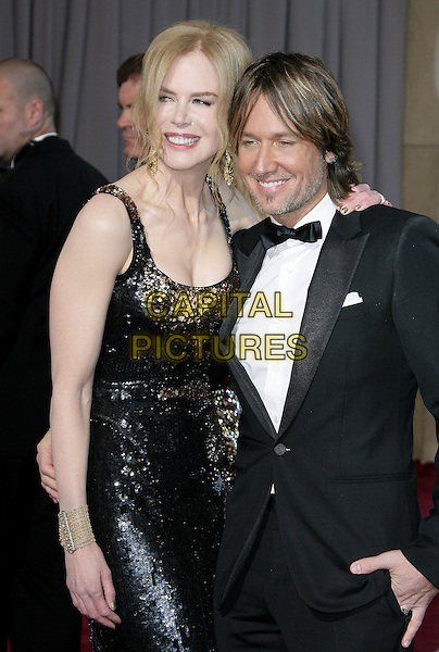 Nicole Kidman (wearing Balenciaga) & Keith Urban.85th Annual Academy Awards held at the Dolby Theatre at Hollywood & Highland Center, Hollywood, California, USA..February 24th, 2013.oscars oscars half length black dress gold sequins sequined sleeveless smiling married husband wife cuff bracelet black tuxedo white shirt.CAP/ADM.©AdMedia/Capital Pictures.