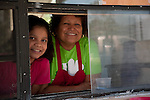 Small Business owner mother and daughter smile out of the taco stand window.