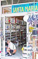 A shop with souvenirs for pilgrims, with things for sale. Madonna statue, rosary beads, post cards, umbrellas... Shop called Santa Marisa Shop. A woman kneeling looking on things to buy. Medugorje pilgrimage village, near Mostar. Medjugorje. Federation Bosne i Hercegovine. Bosnia Herzegovina, Europe.