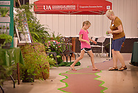 NWA Democrat-Gazette/BEN GOFF &bull; @NWABENGOFF<br /> Hayley Hodson, 8, of Cave Springs helps Melissa Stratton of Bella Vista tape down a meandering path through the Benton County Master Gardeners booth on Monday Aug. 10, 2015 at the Benton County Fairgrounds &amp; Expo Center in Bentonville. Events at the Benton County Fair run through Saturday.