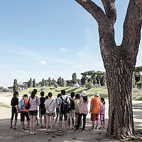 A group of tourists listens to the explanations of the guide at Circo Massimo, Rome, Italy.
