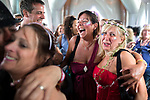 "© Joel Goodman - 07973 332324. 06/08/2017 . Macclesfield , UK . Friends look on at the wedding ceremony for Debbie and Andrew Tideswell , 47 and 56 respectively, from Northwich, ""officiated"" by ""Revd Duncan Pritchard"" at an inflatable church . The couple met in the queue at the festival last year . The Rewind Festival , celebrating 1980s music and culture , at Capesthorne Hall in Siddington . Photo credit : Joel Goodman"