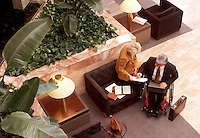 Handicapped businessman and businesswoman work in office building lobby.
