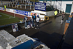 Programme sellers awaiting spectators at the home end of the ground before Greenock Morton take on Stranraer in a Scottish League One match at Cappielow Park, Greenock. The match was between the top two teams in Scotland's third tier, with Morton winning by two goals to nil. The attendance was 1,921, above average for Morton's games during the 2014-15 season so far.