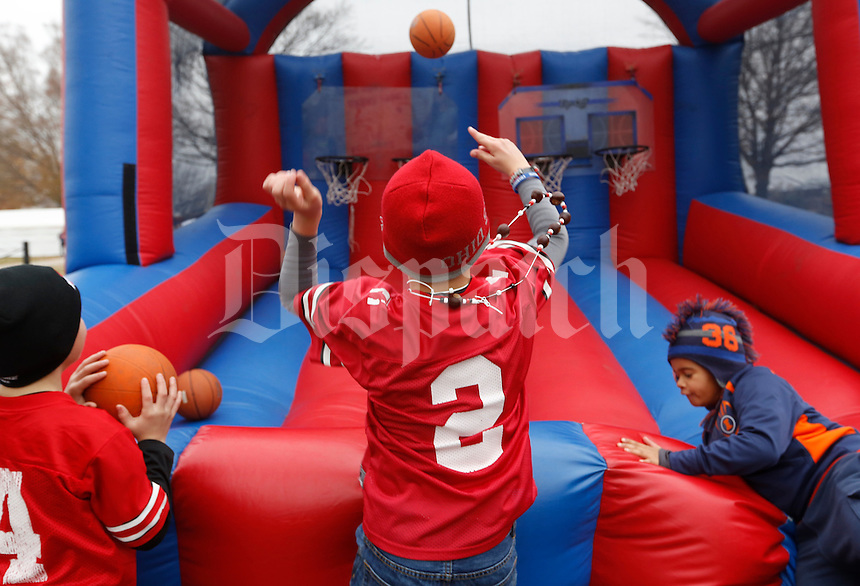 Blaine Belcher, 10, center, shoots a basket while playing in the Illini Street Festival with Elijah Lawrence, 10, left, and Treyton Smith, 8, right, before Saturday's NCAA Division I football game between Ohio State University and Illinois at Memorial Stadium in Champaign, Il., on November 16, 2013. (Barbara J. Perenic/The Columbus Dispatch)