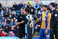 Jerell Sellars of Wycombe Wanderers (2nd left) is spoken to my Referee, Mr Iain Williamson during the Sky Bet League 2 match between Wycombe Wanderers and Mansfield Town at Adams Park, High Wycombe, England on 25 March 2016. Photo by David Horn.