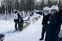 Acting as trail guards, volunteers Bonnie Anthony (L) and Jennie Schoberg, watch as Melissa Owens rounds a corner   in Anchorage on Saturday March 1st during the ceremonial start day of the 2008 Iidtarod Sled Dog Race.