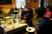 March 25, 2009. Carrboro, NC.. On a nearly weekly basis, Vimala Rajendran, and volunteers, make a community dinner at her house that is open to all comers. A donation is asked for, but all are welcome to eat. . Guests fill the living room as Vimala talks on the phone.