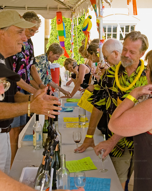 Volunteers chat with visitors while pouring at Breaux Vineyards' annual Key West Fest.