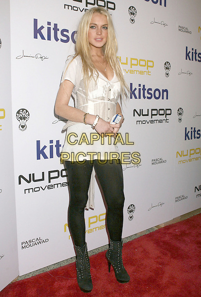 LINDSAY LOHAN.Nu Pop Movement Watch Launch Party at Kitson Men, West Hollywood, California, USA..November 12th, 2009.full length waist belt cincher corset bustier over  black leggings cream white t-shirt top tights ankle boots studs studded.CAP/ADM/MJ.©Michael Jade/AdMedia/Capital Pictures.