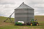 John Deere 8630 tractor (mid 1970s) next to a grain storage tank in Washington's Palouse.