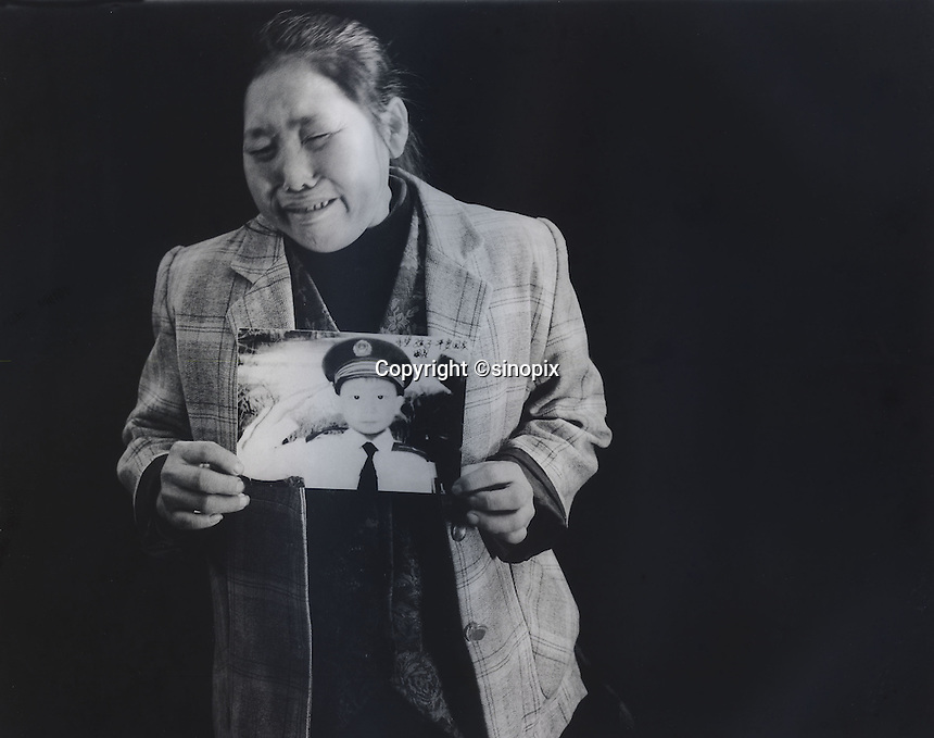 "Mrs Xiang, 40, holds a picture of her son Ren Pan, who was 4 and half years old when he was stolen 9th September 2003. The message reads; ""Hope my son can come back home safe.""<br /> Jun 2007<br /> <br /> photo by Richard Jones / Sinopix"