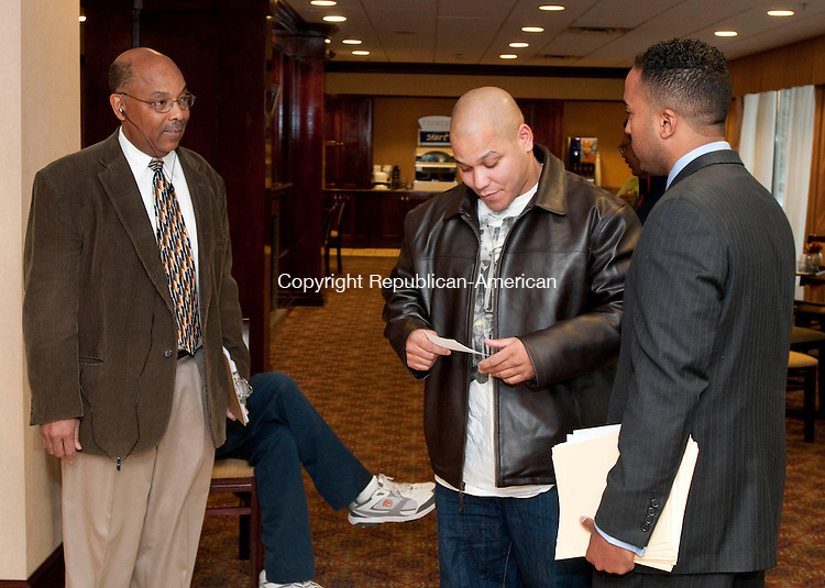 WATERBURY, CT, 11 NOVEMBER 2010-111110JS09-Victor M. Diaz, right, talks with Samuel Alvarez of Waterbury, center,  as he and current NAACP Greater Waterbury Branch President Monroe Webster, left, greet voters as they file into the Holiday Inn Express in Waterbury on Thursday to vote in officers. DIaz was challenging Webster for the leadership of the chapter. <br />  Jim Shannon Republican-American