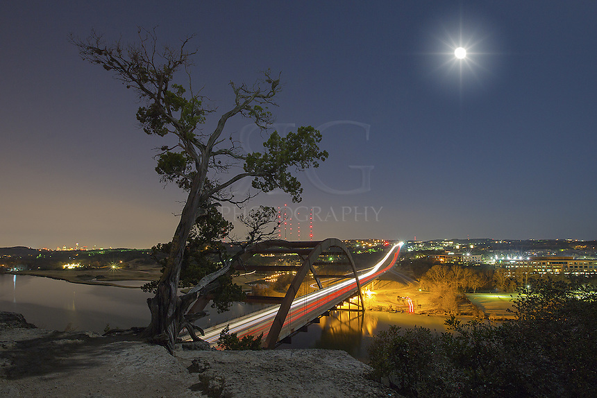 On a clear January night, a nearly full moon shines over the 360 Bridge, also known as Pennybacker Bridge. In the distance rises the Austin skyline. This spot is a favorite of Austin locals and offers spectacular views of the Colorado River, the bridge, downtown Austin, and the distant Texas Hill Country to the west.