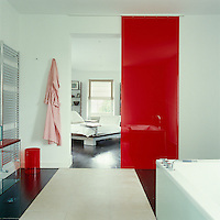 A sliding red Plexiglas door divides the ensuite bathroom from the master bedroom
