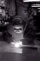 Welder at work in a machine shop.