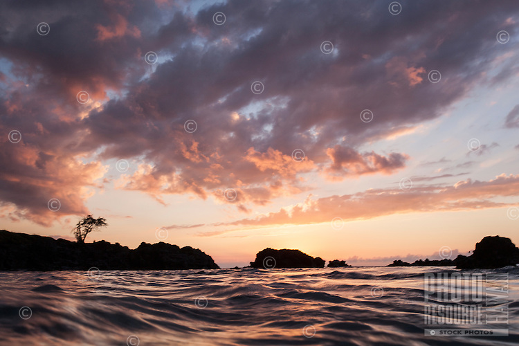 The colors of a vivid sunset reflect off the water at Waimea Bay, North Shore, O'ahu.
