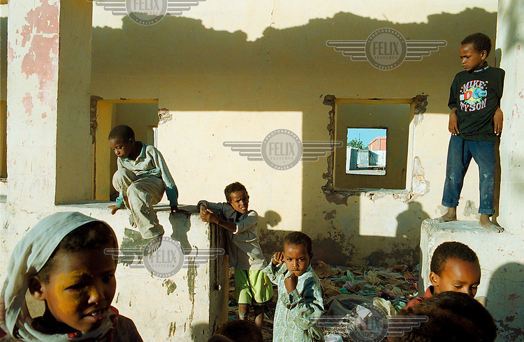 Children play in a demolished house that is also used as a rubbish dump..