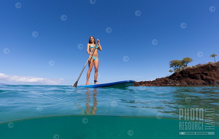 A woman enjoys standup paddling at Black Rock, Maui.