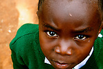 A curious student stares at my camera during a break at Hamomi Children's Centre in Nairobi, Kenya