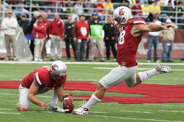 Washington State punter, Reid Forrest (#8), holds for placekicker Nico Grasu (#18) during the Cougars Pac-10 conference tilt with Oregon at Martin Stadium in Pullman, Washington, on October 9, 2010.  The Ducks broke open a tight game in the fourth quarter to win, 43-23.
