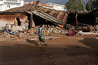 Pictured: A woman walks past a collapsed building.<br />