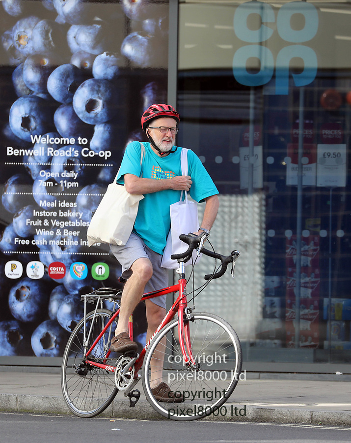 Pic shows: Jeremy Corbyn gets his leg over - just about, an awkward manoeuvre to tackle particularly with two heavy shopping bags. <br /> <br /> <br /> Jeremy Corbyn took a day off from his Brexit negotiations to do some shopping at his local Co-Op - perhaps stocking up on provisions ahead of the North London Derby - he is a keen Arsenal supporter and was perhaps planning to watch them play Tottenham FC<br /> <br /> Despite his spindly looking legs he keeps fit by cycling and working out in the park. <br /> <br /> He was also able to keep perfectly balanced by carrying two heavy shopping bags full of food and drink.<br /> <br /> <br /> <br /> <br /> <br /> picture by Gavin Rodgers/ Pixel8000