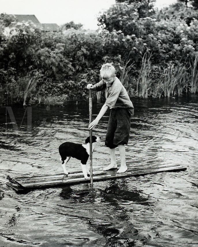 Boy and his dog rafting on pond. 1950's<br />