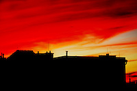 Silhouette of city scapes with an orange and yellow late afternoon sky as backdrop.