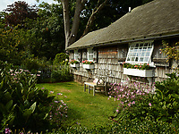 To the rear of the cottage is a pretty garden with a lawn. A wooden bench provides a quiet spot to sit and enjoy the flowers.