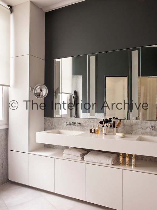 A stylish modern bathroom in dark grey and neutral. A mirror is placed above two washbasins in a wall-mounted unit.