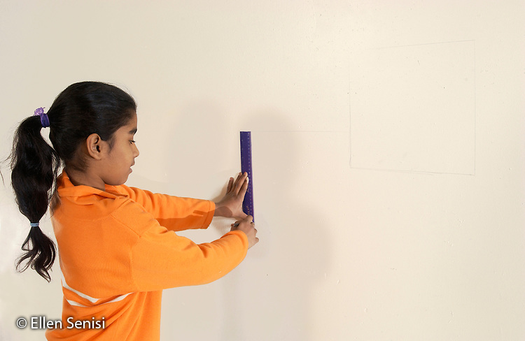 MR / Schenectady, NY .Dr. Martin Luther King, Jr. Magnet School of Math, Science, Technology, and Invention / urban public school.Girl (9, East Indian American) uses a ruler to draw geometric shapes on empty art room wall..MR:  Rob13.©Ellen B. Senisi