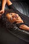 Young African American woman laying on sofa