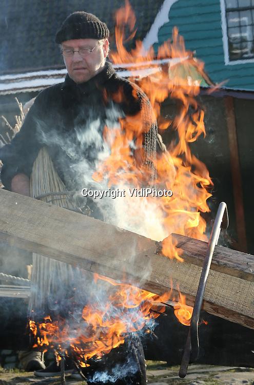 Foto: VidiPhoto<br /> <br /> ARNHEM - In het Nederlands Openluchtmuseum is maandag de eerste plank vervaardigd voor een zogenoemde kubboot, een bijboot van een Spakenburgse botter. Dat gebeurt onder leiding van de 58-jarige Henk van Halteren, voormalig eigenaar van de botterwerf in Spakenburg. De zevende generatie botterbouwer heeft zijn werf overgedaan aan zijn personeel en is nu in dienst van het Openluchtmuseum om het ambacht van botter bouwen te leren aan anderen en te documenteren. In 1986 werd voor het laatst een nieuwe kubboot (en botter) gebouwd in Spakenburg. Nu vinden er alleen nog restauraties plaats. Nu gebeurt dat in Arnhem en ook nog eens op authentieke wijze. Om de juiste krommingen (torsing) in het houtwerk te kunnen krijgen worden de eiken planken uit Denemarken aan de onderzijde verhit en een de bovenkant nat gemaakt. Tijdens de winteropenstelling tot en met 17 januari krijgen de bezoekers een voorproefje van het werk. De offici&euml;le start is pas in april. De boot moet in oktober 2016 gereed zijn.
