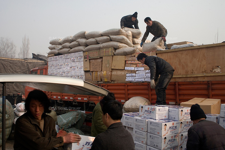 Men load trucks for shipment along the so-called New Silk Road in Urumqi, Xinjiang, China.