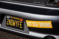 "Spotted in a parking lot, a custom plate with bumper sticker:  ""2NDWYFE""  ""NOT SELF DRIVING'"