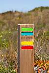 Footpath marker way mark sign painted in green, blue, yellow and red stripes for the Ruta Vicentina long distance footpath, the Fisherman's Trail and Historical Way, within the Southwest Alentejo and  Vicentina Coast Natural Park, south west Portugal, southern Europe